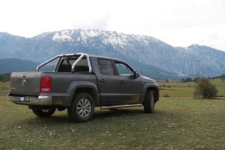 Ein Pick Up Jeep steht auf einer weiten Wiese im Taurusgebirge. Auf den Bergen liegt noch Schnee.