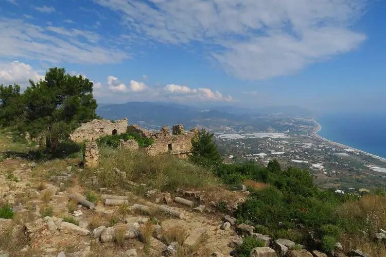 Der Blick auf die Kolonnade und das Badehaus in den Ruinen der antiken Stadt Syedra. Der Blick geht weit auf das Meer und die umliegenden Dörfer hinaus.