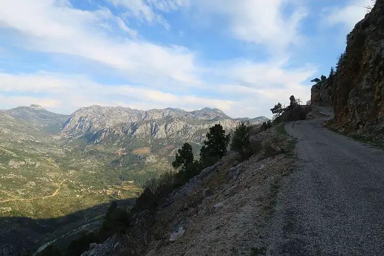 Eine Bergstraße mit einem weiten Ausblick auf das darunterliegende Tal.