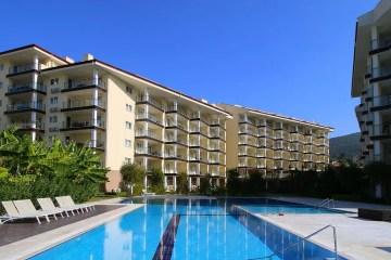 Pool im Ruhebereich und eines der Haupthäuser des Ramada Resort Kusadasi & Golf