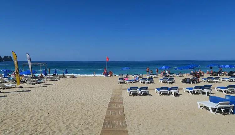 Strandliegen am Kleopatrastrand und das türkisblaue Meer.