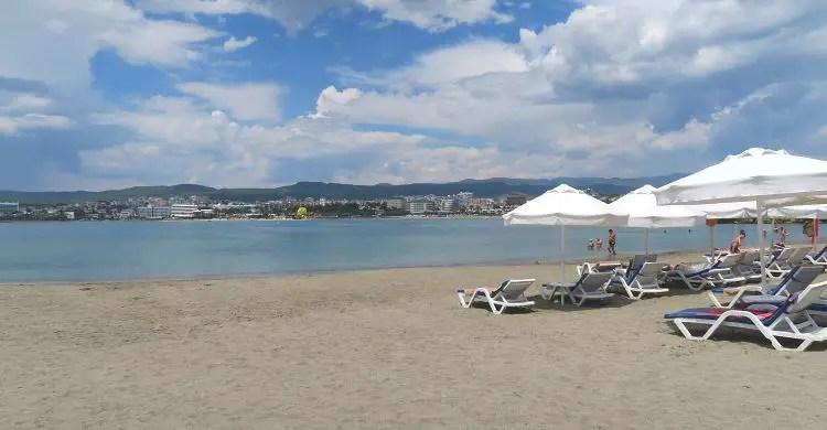 Strandliegen, Sonnenschirme und Sandstrand