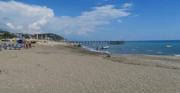 Sandstrand, Meer, Liegestühle und Sonnenschirme mit Badegästen