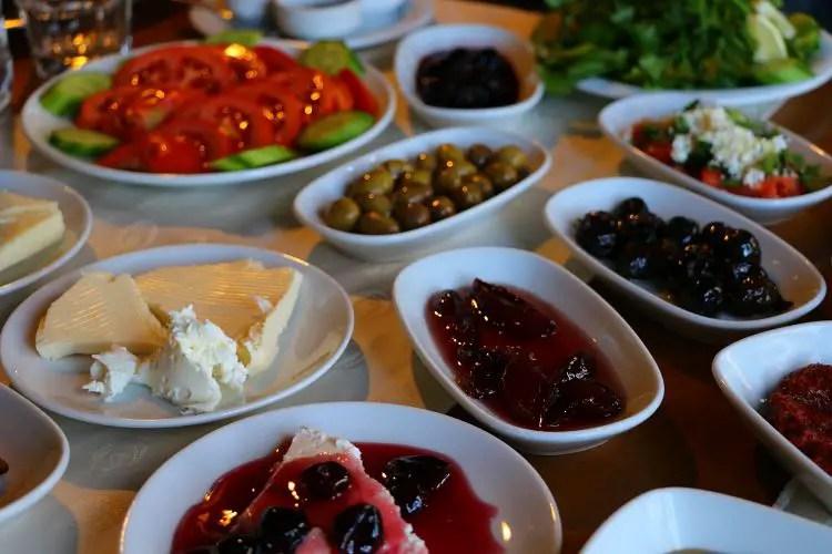 Teller und Schalten mit den einzelnen Zutaten eins türkischen Frühstücks. Tomaten, Käse, Gurken, Marmelade, Oliven
