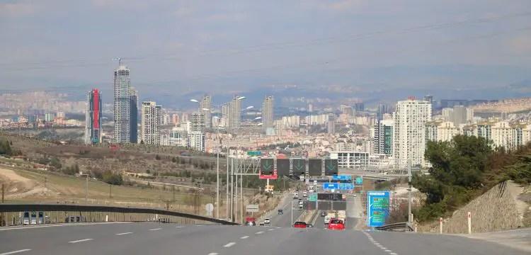 Mehrspurige Autobahn mit Hochhäusern im Hintergrund