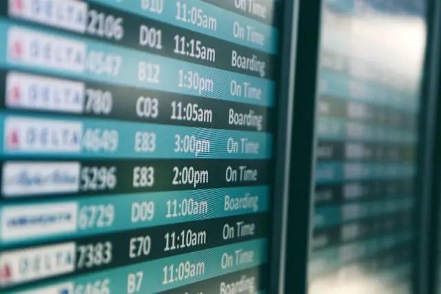 Anzeigentafel auf einem Flughafen. Die Farben sind in blau und schwarz gehalten. Die Schrift ist weiß. Es ist nur ein kleiner Teilbereich zu sehen. Das Bild ist aus etwa einem Meter Entfernung aufgenommen worden.