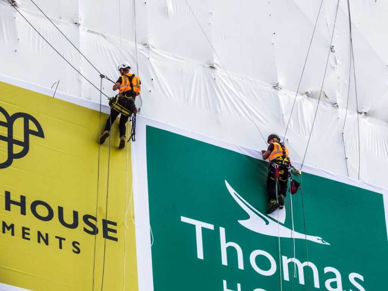 Rope access technicians installing banner on to scaffolding sub frame on shrink-wrap