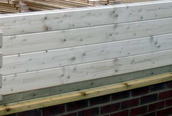 A foundation beam runs around the perimeter of the log cabin