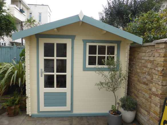 One of our Onyx log cabins, a small building measuring 2.6 x 2.2m. Really nicely painted in pastel colours
