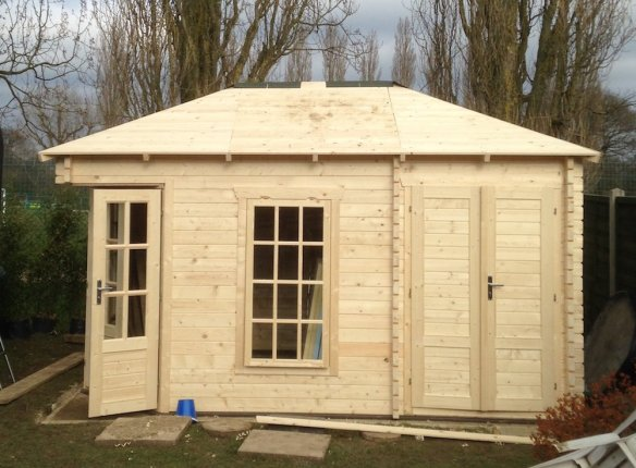 Roof structure and roof boards complete on a log cabin ready for the final roof covering to be applied.