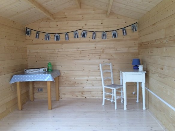 This is the inside of a Lulea Log Cabin, a simple beach hut theme.
