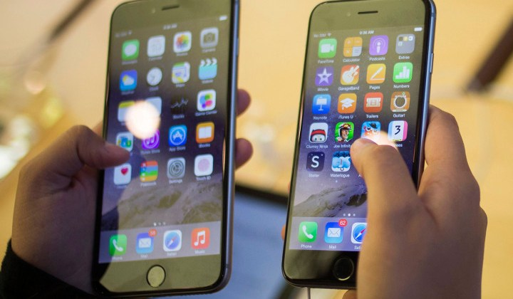 A customer holds an iPhone 6  and iPhone 6 Plus after the phones went on sale at the Fifth Avenue Apple store in New York
