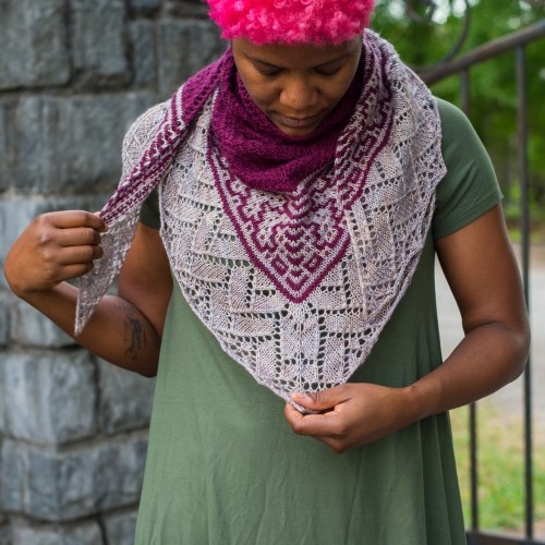 A soft shawl wrapped around the neck featuring mosaic colorwork and lace.