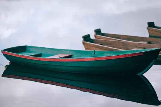wooden boats moored on calm pond water