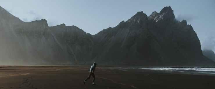 unrecognizable traveler walking on sandy coast near mountains