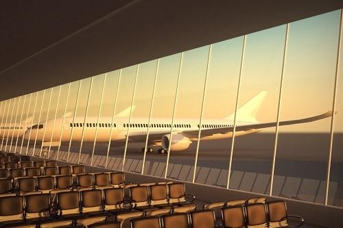 Terminal del aeropuerto moderno con asientos de cuero negro al atardecer. Una gran fachada de vidrio de visión con un avión de pasajeros detrás de él.