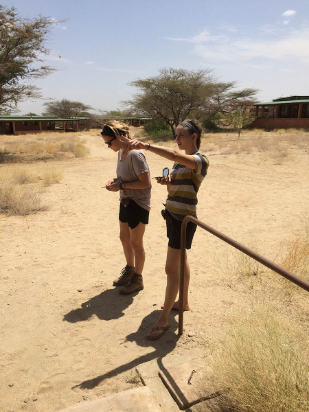 Rachel and Larisa measure the distance and direction between structures. For direction they are using an important geological field tool, a Brunton Compass.
