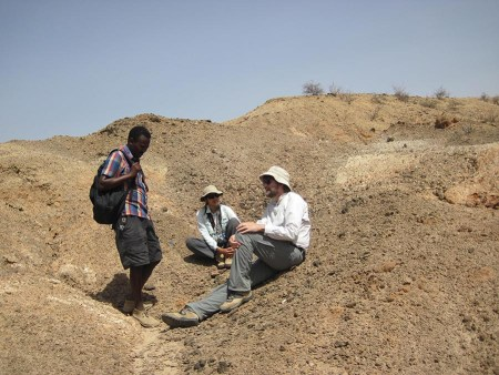 Professional fossil preparator, Chris Kiarie, directs Dr. Fortelius and Linda to a collection of XXX bones he had just found.