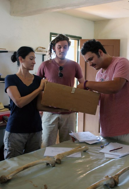 Dr. Rivera, Jamie and Max sort through a box of replica skeletal bits to piece together the human skeleton.