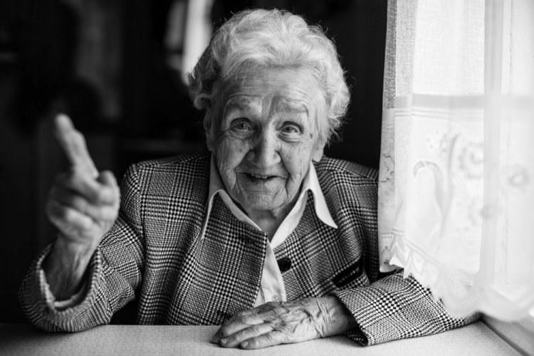 Foto in bianco e nero di anziana signora alla finestra