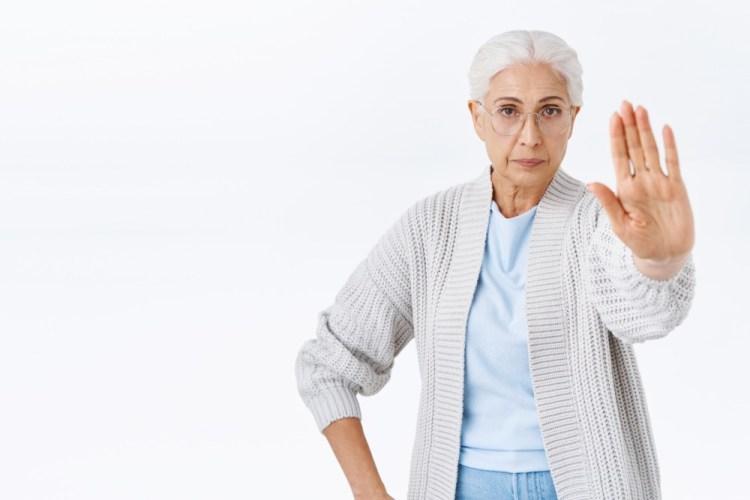 Singora anziana con la mano a stop