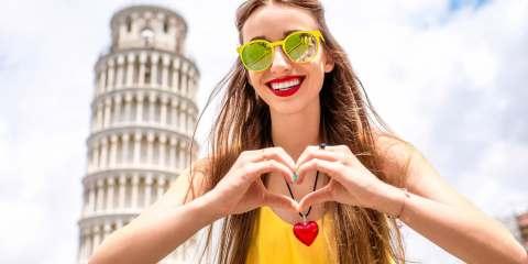 Ragazza con le mani a cuore davanti alla Torre di Pisa durante un'estate in Toscana