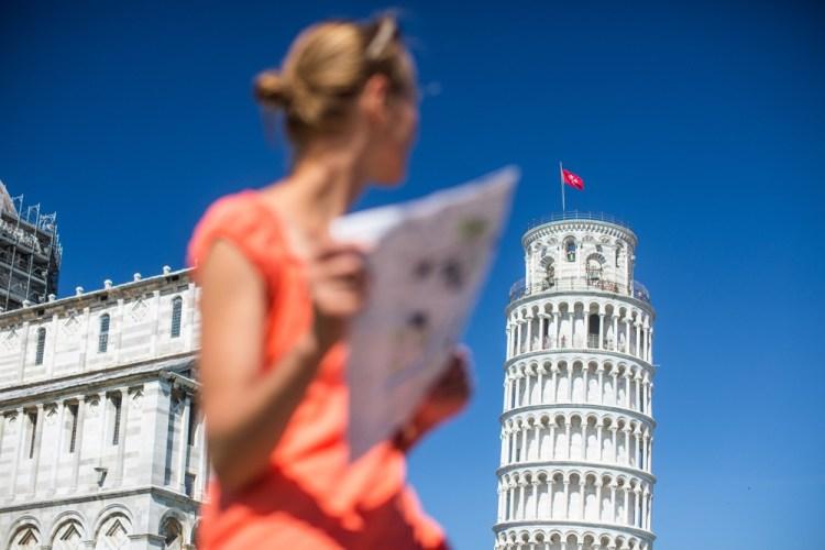 Turista con cartina di fronte alla Torre di Pisa