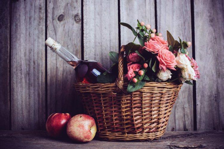 Bottiglia di vino rosato in cesto di vimini con rose e mele