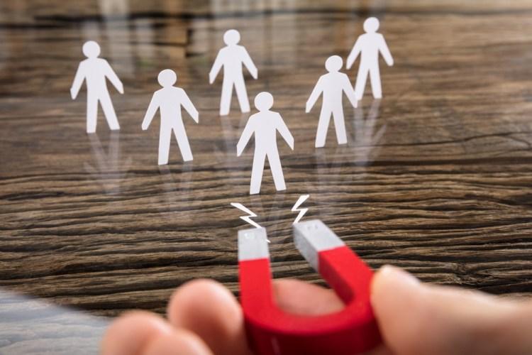Un magnete attrae omini di carta per rappresentare il concetto di lead generation