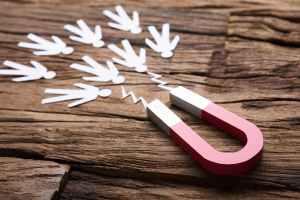 Magnete su tavolo di legno attira omini stilizzati per rappresentare il concetto di lead generation