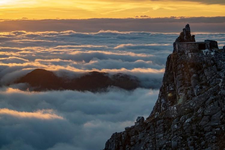 Un picco delle Alpi Apuane al tramonto con un mare di nebbia sottostante