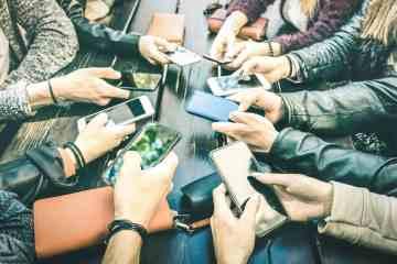 Tanti mani con cellulare su un tavolo di legno