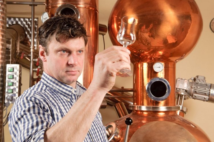 Distillatore con bicchiere in mano davanti ad alambicco di rame