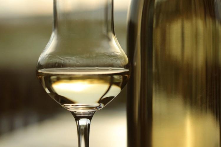 Bicchiere di grappa vicino alla sua bottiglia