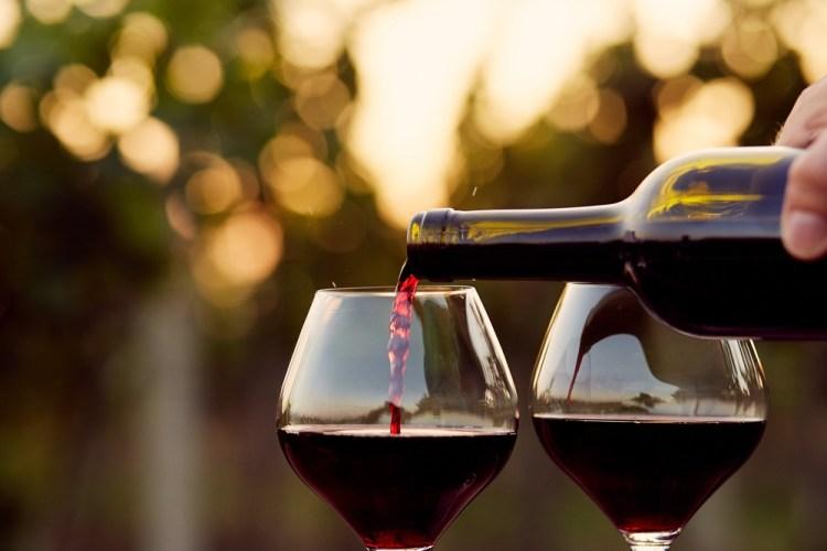Versare vino rosso da una bottiglia in due calici al tramonto