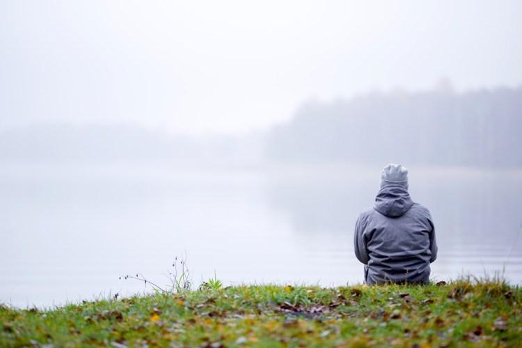 Ragazzo seduto sulle rive di un lago guarda la nebbia salire