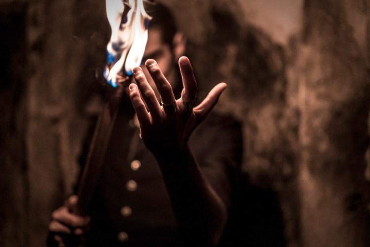 Mago con vestiti vintage evoca fuoco dalle dita della mano