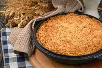 Torta appena sfornata su tagliere di legno con grano e tovaglia a quadretti