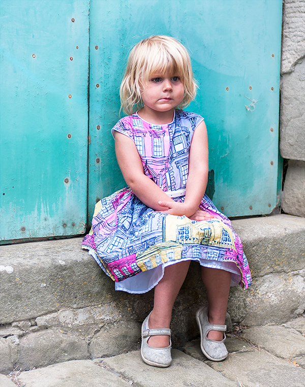 little girl sitting on an old step