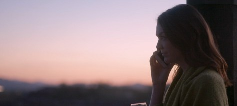 A woman talks on her cell phone. The sun sets behind her.