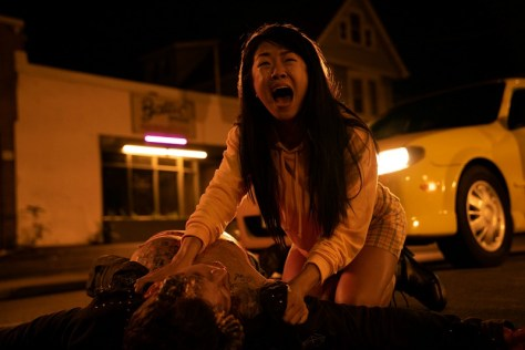 A woman screams while crouching over a dead body.