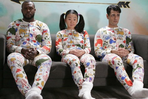 Three people sit on a couch, side by side, wearing the same clothes.