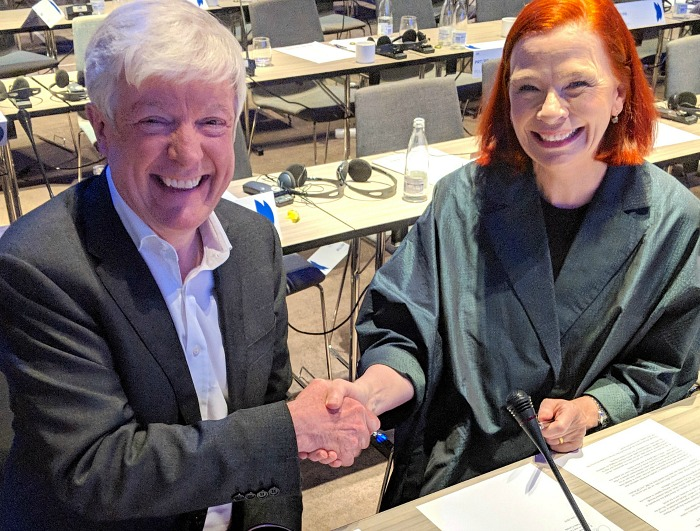 Two people, smiling, shake hands.