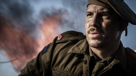 A male soldier looks into the distance. A fire burns behind him.