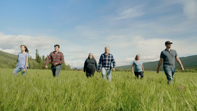 A group of people walk through a field.