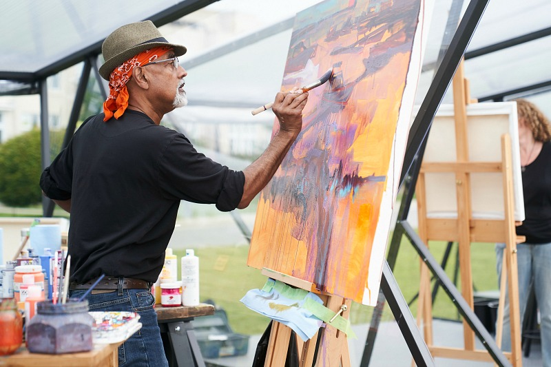 A man paints at an easel.