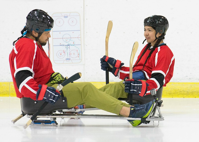 Two men play sledge hockey.