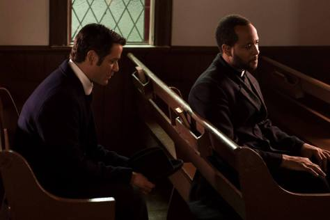 Two men sit in a church.
