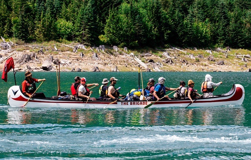 A group of people paddling a canoe.