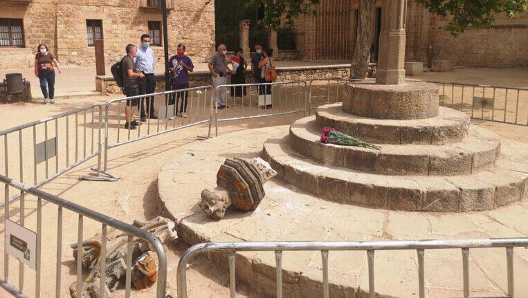 Un home s'enfila i tira a terra la creu medieval del Monestir